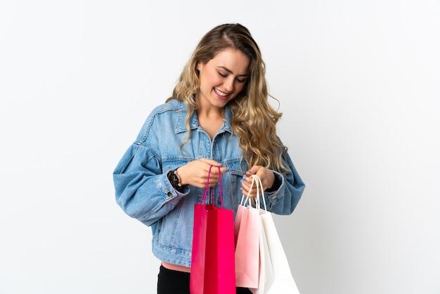 Giovane donna brasiliana isolata sui sacchetti della spesa bianchi della tenuta e guardando al suo interno