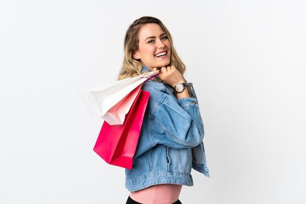 Giovane donna brasiliana isolata su borse della spesa bianche della holding e sorridente