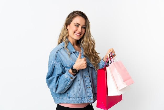 Giovane donna brasiliana isolata sui sacchetti della spesa bianchi della tenuta e con il pollice in su
