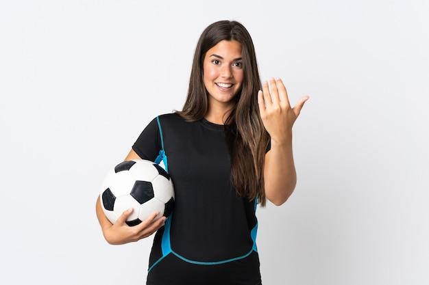 Giovane donna brasiliana isolata sul muro bianco con pallone da calcio e facendo gesto in arrivo