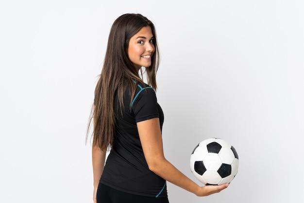 Giovane donna brasiliana isolata sul muro bianco con pallone da calcio