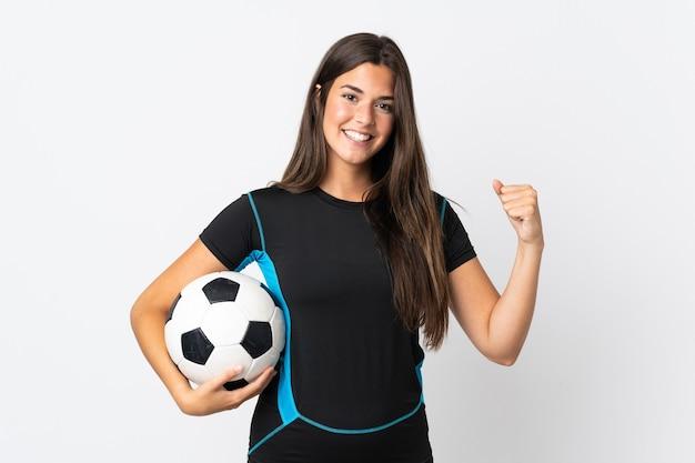 Giovane donna brasiliana isolata su bianco con pallone da calcio che celebra una vittoria