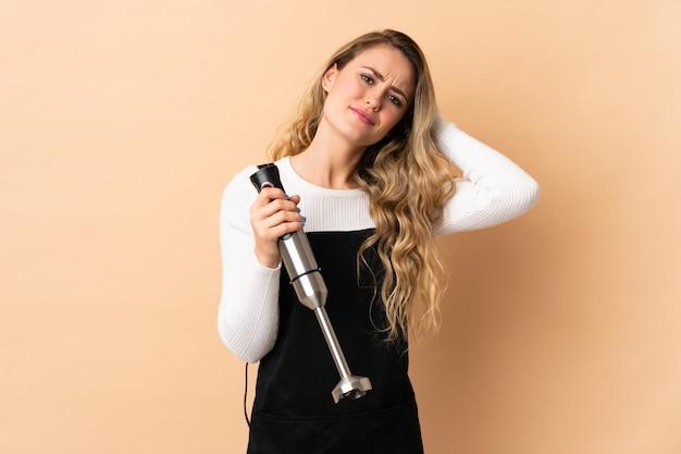 Giovane donna brasiliana utilizzando frullatore a immersione isolato su beige avendo dubbi