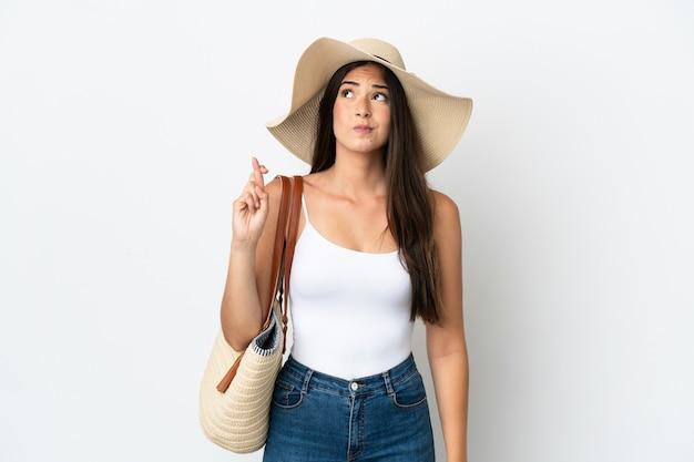 Giovane donna brasiliana con pamela che tiene in mano una borsa da spiaggia isolata su sfondo bianco con le dita incrociate e augurando il meglio