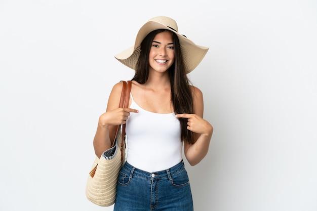 Giovane donna brasiliana con pamela che tiene in mano una borsa da spiaggia isolata su sfondo bianco con espressione facciale a sorpresa