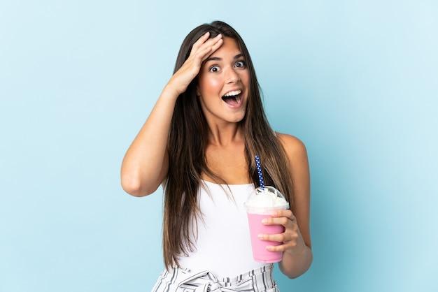 Giovane donna brasiliana con frullato di fragole isolato su sfondo blu con espressione di sorpresa