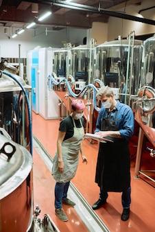 Giovane maestro di birra che indica il documento mentre spiega alla sua subordinata quali ingredienti dovrebbe usare per la produzione di birra