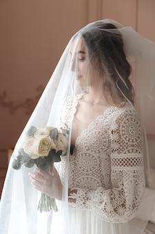 Giovane sposa in un bellissimo abito di pizzo boho sotto un lungo velo.