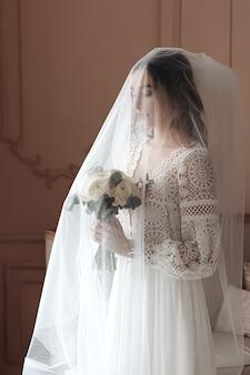 Giovane sposa in un bellissimo abito in pizzo boho sotto un lungo velo.