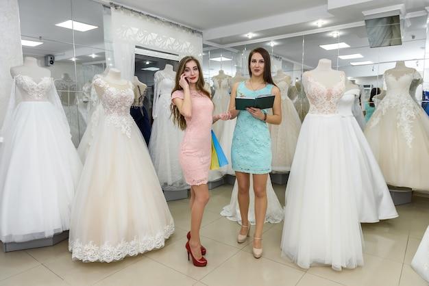 Giovane sposa prenotazione abito da sposa in rivenditore in salone