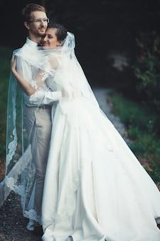 Una giovane sposa e lo sposo in piedi insieme all'aperto, estate