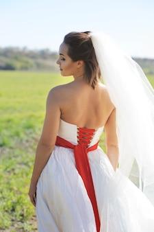 Ritratto all'aperto della giovane sposa in vestito bianco contro il campo verde, vista posteriore