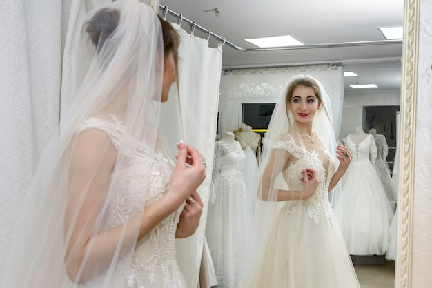 Giovane sposa in salone che guarda nello specchio la sua riflessione