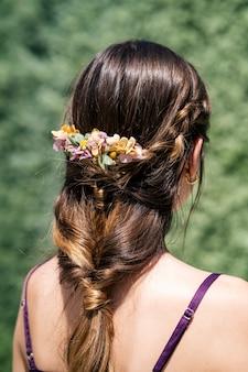 Giovane sposa con capelli biondi bella acconciatura e bella corona di fiori naturali
