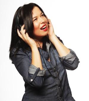 Giovane donna bruna brillante con musica d'ascolto delle cuffie