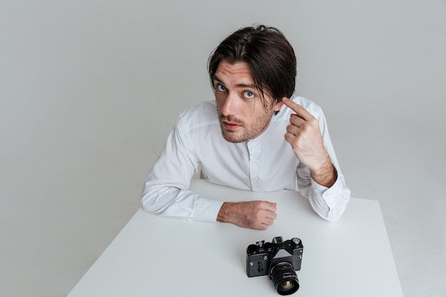 Giovane uomo brunetta con le setole che indica al suo orecchio mentre è seduto al tavolo isolato sul muro grigio