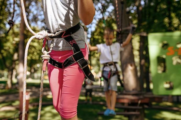 Giovane fratello e sorella si arrampicano nel parco avventura