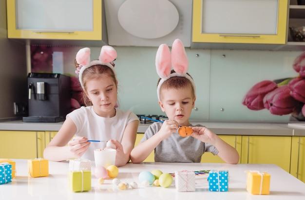 Un giovane fratello e sorella con le orecchie di coniglio in testa dipinge le uova di pasqua a casa in cucina. preparandosi per le vacanze di pasqua