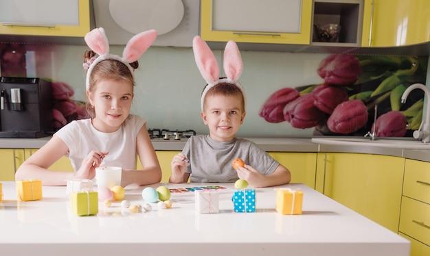 Un giovane fratello e una sorella con le orecchie di coniglio in testa dipingono le uova di pasqua a casa in cucina. preparandosi per le vacanze di pasqua