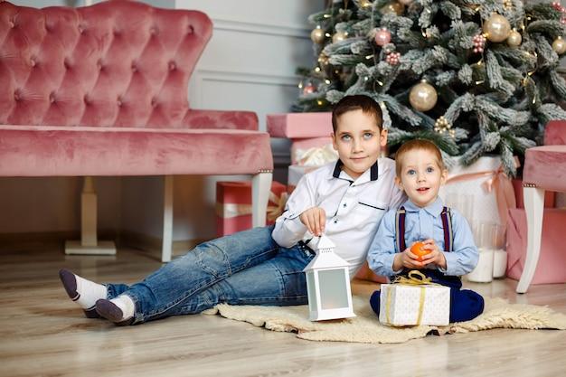 Giovani fratelli vicino all'albero di natale