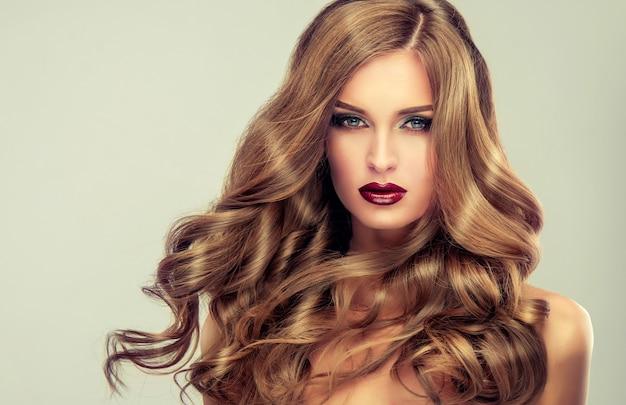 Giovane donna dai capelli castani con acconciatura da sera elegante e voluminosa. bellissima modella con capelli lunghi, folti e ricci e trucco vivido con rossetto rosso. arte dell'acconciatura, cura dei capelli e prodotti di bellezza.
