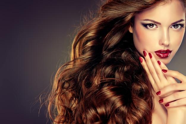 Giovane donna dai capelli castani con acconciatura da sera elegante e voluminosa. bellissima modella con capelli lunghi, folti e ricci e trucco vivido con rossetto rosso. arte, trucco e manicure per parrucchieri.