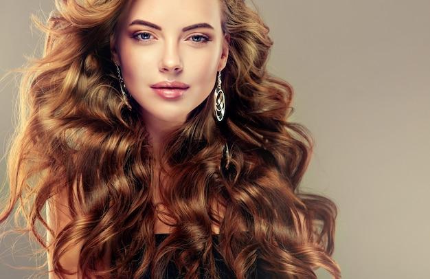 Giovane donna dai capelli castani con elegante acconciatura voluminosa e crespa
