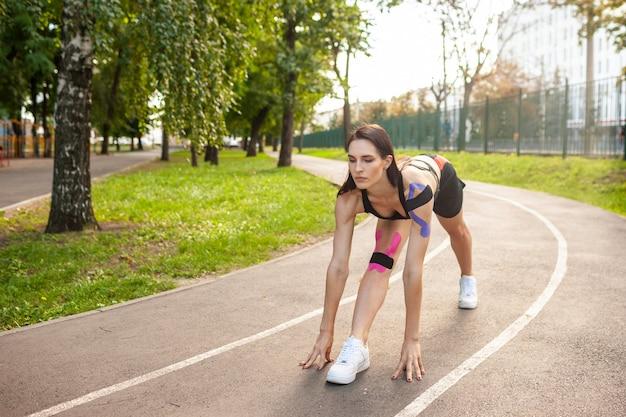 Giovane donna bruette con un corpo perfetto che si riscalda all'aperto e allunga le gambe e una splendida ragazza in forma che indossa un abito sportivo nero che si allena nel parco estivo