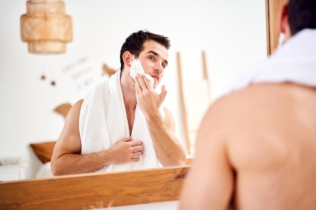 Il giovane brunet spalma il viso con la schiuma da barba mentre sta in piedi nella vasca da bagno vicino allo specchio
