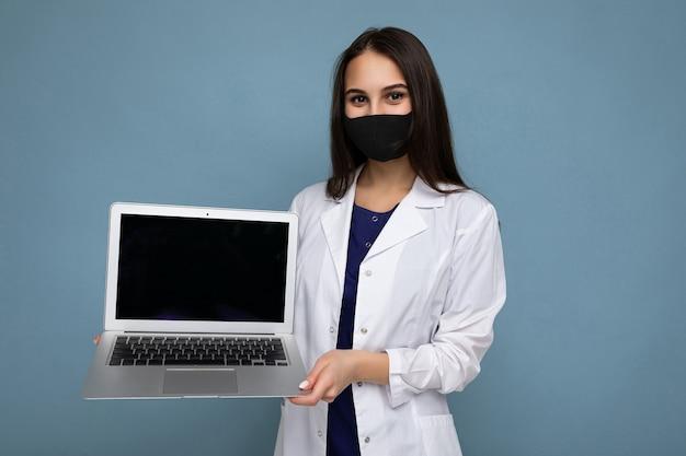 Giovane donna brunetta che indossa camice bianco medico e maschera nera che tiene in mano un computer portatile e guarda la telecamera isolata su sfondo blu muro