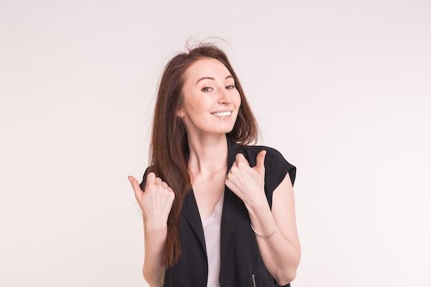 La giovane donna asiatica del brunette che mostra i pollici aumenta il gesto su bianco