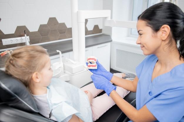Giovane assistente bruna in uniforme blu e guanti che mostra i denti falsi alla bambina e le spiega di spazzolarli correttamente