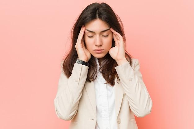 Giovane donna d'affari bruna contro un muro rosa toccando le tempie e avere mal di testa.