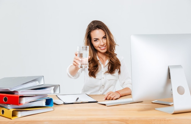 Giovane imprenditrice bruna seduta al tavolo con il computer che tiene in mano un bicchiere d'acqua isoltaed sullo sfondo bianco