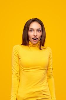 Giovane bruna in dolcevita giallo casual, fissando la telecamera con la bocca aperta e l'espressione del viso scioccato su sfondo giallo vivido