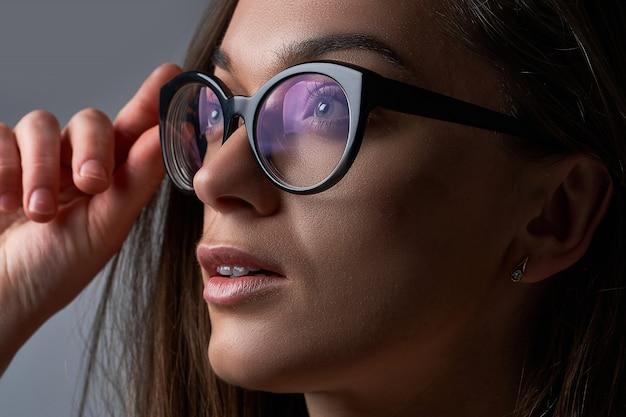 Giovane femmina caucasica castana che indossa i vetri neri della struttura per visione