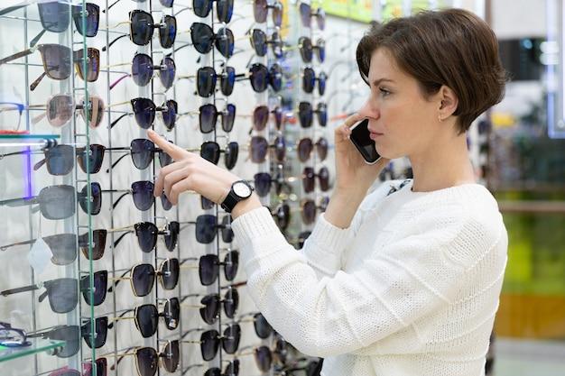 La giovane bruna sceglie occhiali da sole, vetrina che vende ottiche di qualità per la visione.