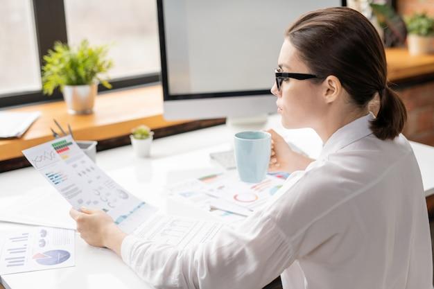 Giovane brunetta economista in camicia bianca e occhiali da vista guardando la carta finanziaria e bere durante il lavoro