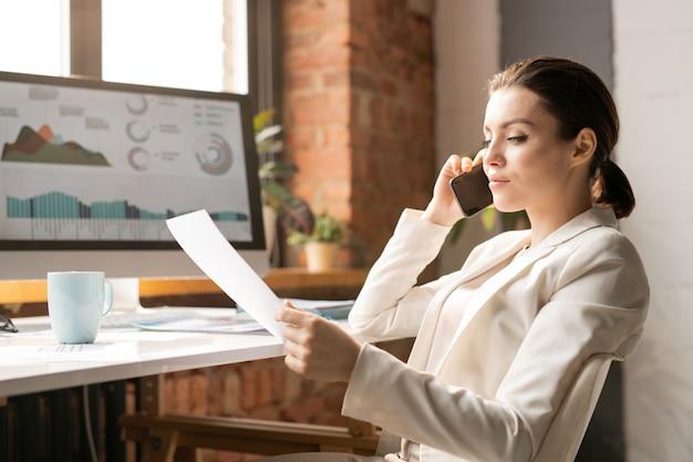 Giovane bruna in un elegante abito bianco, parlando al telefono mentre era seduto alla scrivania e guardando attraverso i dati finanziari nel documento