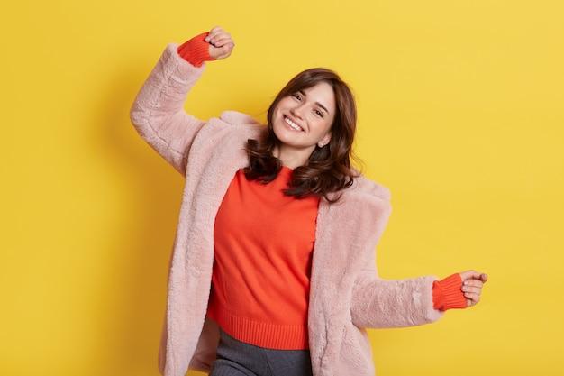 Giovane ragazza bruna europea eccitata che indossa un cappotto di pelliccia caldo, braccia in movimento ai suoni della musica, con un sorriso a trentadue denti, che esprime felicità, si trova isolato sul muro giallo