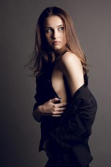 Giovane donna bruna in jeans reggiseno nero e giacca di pelle su sfondo grigio