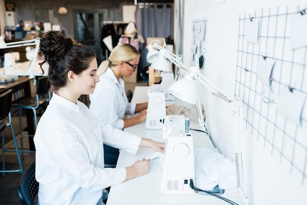 Giovane donna castana in camicia bianca che si siede dalla macchina da cucire elettrica mentre lavora