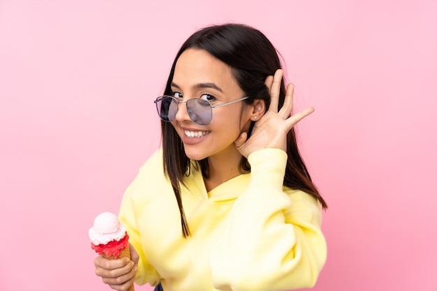Giovane ragazza castana che tiene un gelato della cornetta sopra la parete rosa isolata che ascolta qualcosa mettendo la mano sull'orecchio
