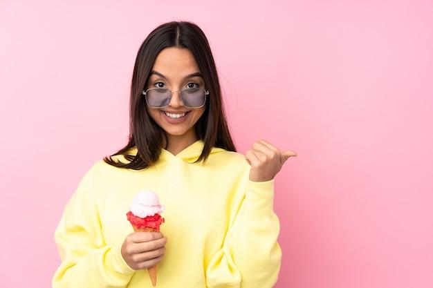 Giovane ragazza castana che tiene un gelato della cornetta isolato