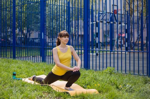 Una giovane ragazza bruna sta praticando sport su una stuoia per strada. la ragazza in abiti sportivi si sta allenando sul prato.