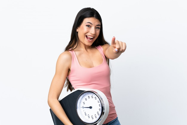 Giovane ragazza castana sopra la parete bianca isolata che tiene una pesa e che indica la parte anteriore