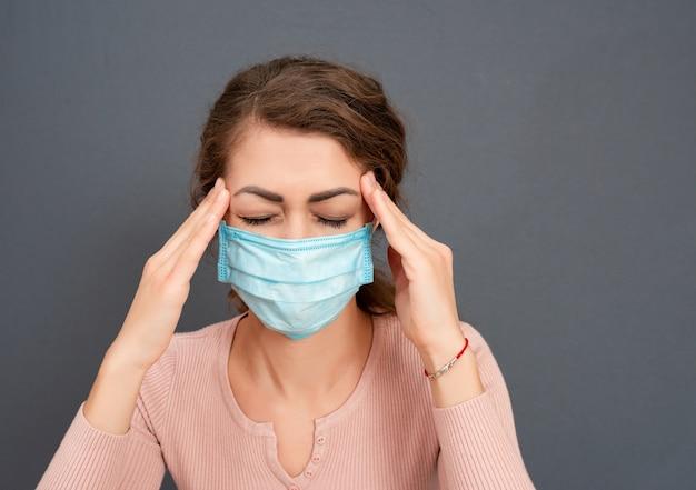 La giovane ragazza castana in maschera medica tiene la testa su una superficie grigia