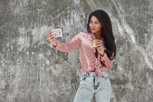 Giovane ragazza castana che sta sulla parete grigia che tiene tazza di caffè caldo che prende la foto del selfie
