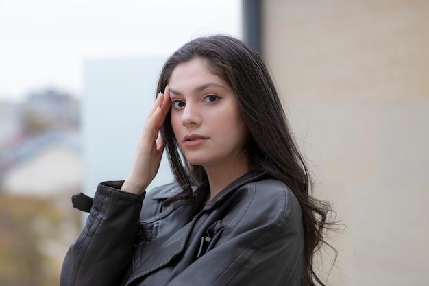 Giovane ragazza bruna in piedi sulla terrazza mentre guarda la fotocamera.