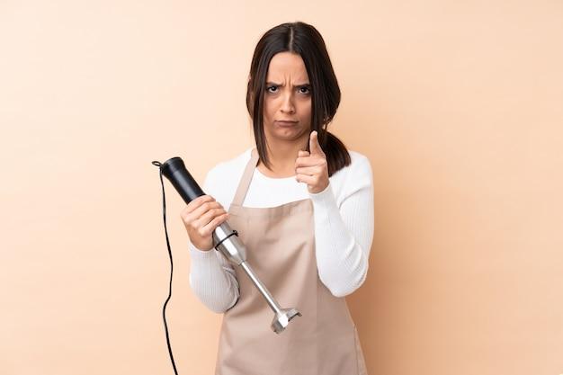 Giovane ragazza castana che usando il miscelatore della mano sopra la parete isolata frustrata e che indica la parte anteriore